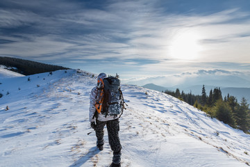 Man is backpacking in winter mountains