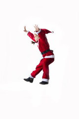 Little caucasian girl dressed as Santa Claus jumping on white background.