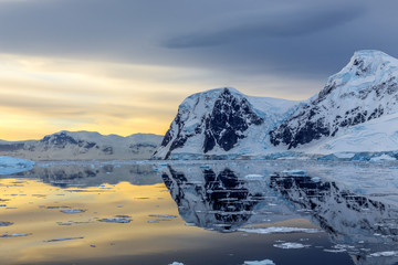Cold still water of antarctic lagoon with glaciers and mountains in the background, Antarctica