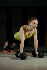 Sporty girl is wrung out with dumbbells in the gym