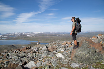 Hiker stands on a rock and enjoys the scenery of the Guolasjavri lake, cairn, summer