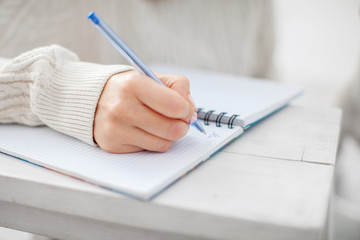 Woman writing pen in notebook