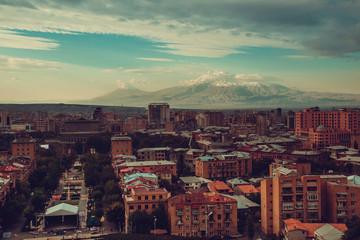 Yerevan cityscape. Travel to Armenia. Tourism industry. Impressive Mount Ararat background. Cloudy sky. Armenian architecture. City tour. Urban landscape. Street view. Sightseeing concept. Copy space.