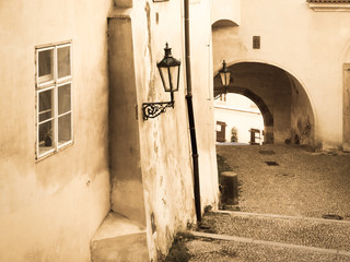 Nooks of Lesser Town in Prague. Old staircase with street lamp and tunnel. Vintage sepia style image. Prague, Czech Republic.