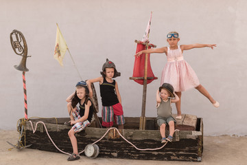 Boys and a beautiful girl play pirates on a toy sailboat built from an old boat