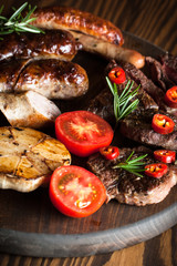 Close-up photo of mixed grilled meat platter. Beef, pork, poultry, sausages, grilled garlic, chili pepper, red tomatoes on wooden rustic background.