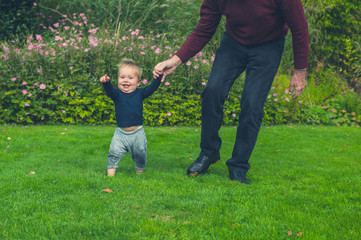 Grandfather running with grandson on lawn