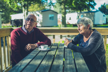 Senior couple drinking coffee in caravan park