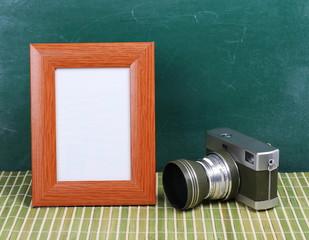 Old camera and picture frame on desk, chalkboard background