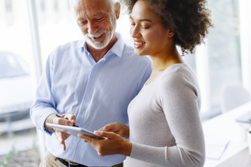 Senior businessman and young african american businesswoman with tablet