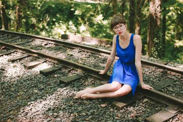 Girl in Blue Sitting on Train Tracks