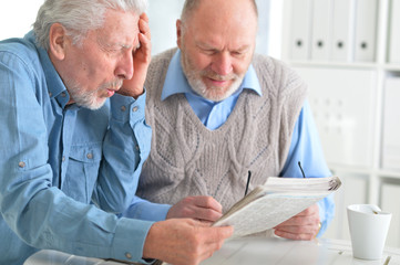 senior men reading newspaper