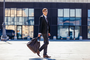 Young Elegant Businessman Walking In Front Of  Modern Building in Milan