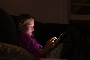 girl with ipad in a dark room