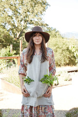 Portrait of woman with fresh garden herbs in her apron