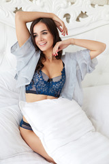 Girl stretching after wake up. Happy young beautiful brunette women in lingerie relaxing in bed