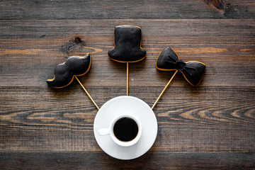 Black tie, mustache and hat cookies on sticks for happy father's day present cookies wooden background top view space for text