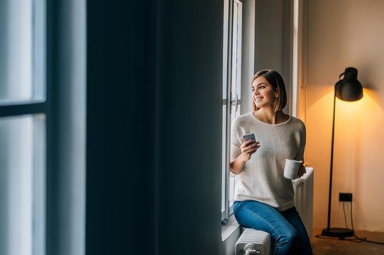 Beautiful smiling woman sitting near window and looking away.