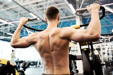 Back view portrait of handsome young man with bare chest pumping  muscles doing exercises on machines in gym