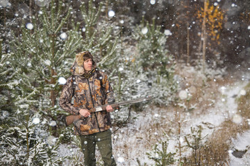 Male hunter with backpack, armed with a rifle, standing in a snowy winter forest. Man looks away. Snowfall in the forest.