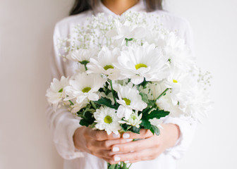 Young woman holding beautiful white flower bouquet