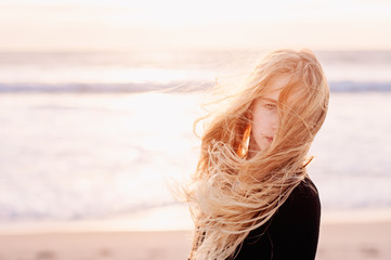 Pre-teenage girl with very windswept long blonde hair at the beach in winter