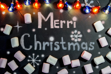 the inscription merry Christmas on black background, surrounded by marshmallows