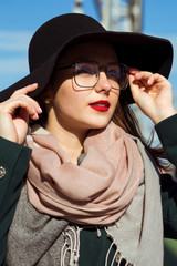 Fashion portrait of pretty young model walking at the city. Woman wearing fashionable hat, scarf and glasses