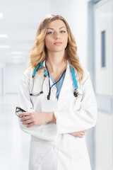 Female doctor in white surgical coat with stethoscope standing on corridor hospital