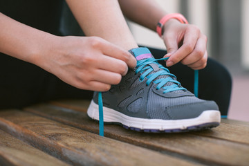 Young woman tying the shoelaces of her fitness shoes on a bench