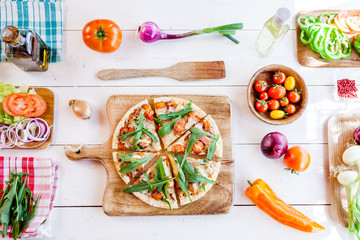 hot fresh homemade traditional italian pizza with cheese, tomatoes and rocked salad on wooden cooking table with ingredients. wallpaper for pizzeria and food concept. top view, flat lay