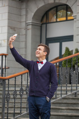 guy in business style clothes on stairway background. Stylish guy. Take pictures of yourself