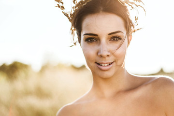 Portrait of a beautiful young woman in sunny fields