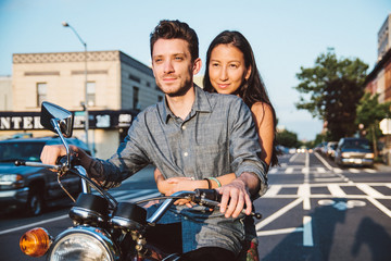 A young woman holds onto a man while they ride a motorcycle in the city