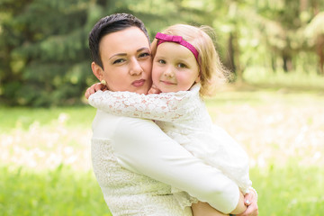 family, children and happy people concept - happy little girl hugging her mother over green background
