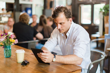 Handsome man using a tablet in a coffee shop