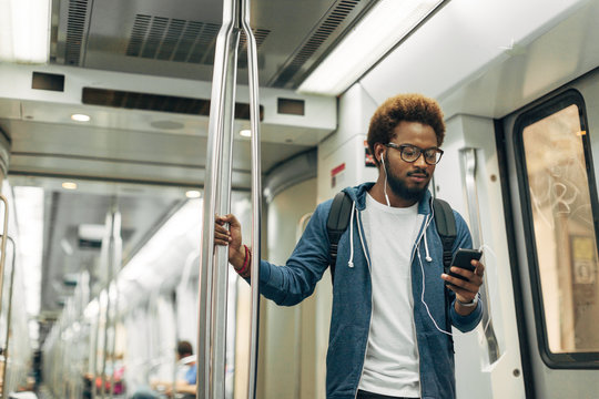 Young afro black man using mobile phone while listening music on the subway train.