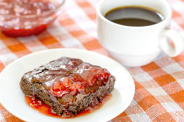 Homemade brownie covered in strawberry jam with a cup of coffee