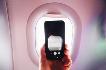 passanger makes photos on the smartphone in the plane