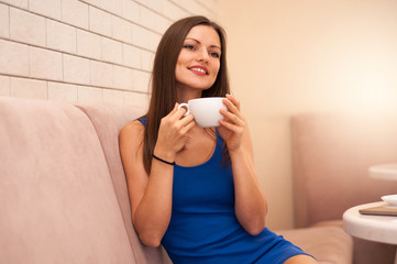 Smiling young beautiful woman with coffee Cup sitting in cafe and looking away