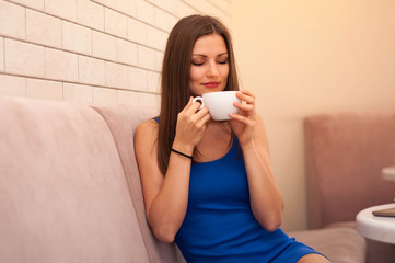 Young beautiful woman enjoying a Cup of coffee, closed her eyes and sniffing the aroma of the beverage