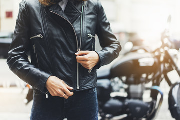 Girl unfastens black leather jacket on background motorcycle in sun flare atmospheric city, hipster biker female hands closeup, motorbike lifestyle, traveler bike route in summer holiday concept