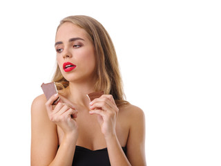 Young blonde girl with a piece of chocolate. Isolated on white background.