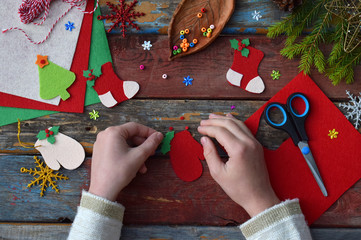 Making of handmade christmas toys from felt with your own hands. Children's DIY concept. Making xmas tree decoration or greeting card. Step 3. Decorate the toy