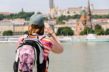 A female tourist with a backpack takes a photograph of Buda Castle in Budapest