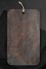 Background with wooden cutting board with black towel on the stone table