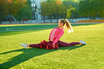 Cheerleading girl in a twine workout, in the morning at sunrise on a field outdoors. Sport, health, fitness