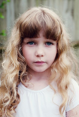 Portrait of a young girl with blonde curly hair
