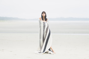 A woman wrapped in a blanket standing on a desolate beach