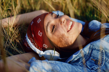 Closeup of young woman listens to music and lying in the meadow